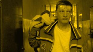 Sfotografowany od pasa w górę mężczyzna opuszcza więzienie. Ma krótkie włosy, ubrany jest w białą koszuklę i zapinaną na zamek kurtkę. Przez ramię ma przerzuconą torbę, na czole okulary