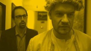 Dwóch mężczyzn w półzbliżeniu. Pierwszy ma na głowie białą teatralną perukę, drugi stoi tuż za nim, ma brodę i okulary w ciemych oprawkach