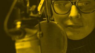 Zbliżenie na mężczyznę w golfie i dużych okularach, który siedzi przed radiowym mikrofonem