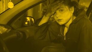 Młoda dziewczyna w roboczym kombinezonie siedzi w samochodzie. Pobrudzoną smarem rękę przykłada do czoła