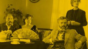 Za stołem siedzą dwaj mężczyźni i kobieta. Kobieta ma wachlarz w ręce. Druga kobieta stoi za mężczyzną, który w ręce trzyma filiżankę