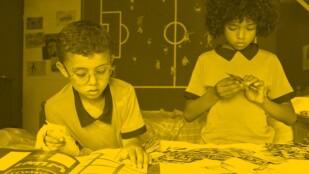 Dwaj mali chłopcy stoją przy łóżku w dziecięcym pokoju. Jeden pochyla się nad albumem z naklejkami, drugi ogląda naklejkę