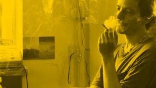 Na zdjęciu w żółtym odcieniu mężczyzna w półzbliżeniu, stoi z prawej strony kadru, pali papierosa. Ma lekko kręcone włosy, ubrany jest w koszulkę z którkim rękawem, na szyi ma sznur koralików. W tle fragment okna, na którego parapecie stoi aparat telefoniczny z faksem