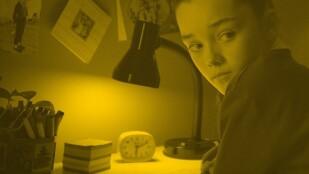 Chłopiec siedzi przy biurku, patrzy przez ramię. Na biurku świeci się lampka, pod nią jest zegarek, stos kwadratowych kartek i pudełko z długopisami