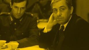 Na zdjęciu w żółtym odcieniu dwóch mężczyzn siedzi przy stole, na którym ustawione są dwie filiżanki. Starszy mężczyzna ubrany jest w ciemny garnitur z białą koszulą i krawatem w kratkę, młodszy ma na sobie wojskowy mundur
