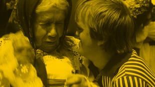 Na zdjęciu w półzbliżeniu starsza kobieta w wiejskiej chustce na głowie z chłopcem ubranym w koszulkę w paski