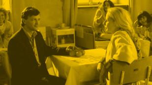 Przy stole w sali szpitalnej siedzi młody mężczyzna w ciemnej marynarce i młoda kobieta z długim, jasnym warkoczem. Patrzą na siebie. Za nimi na łóżkach siedzą trzy kobiety, które na nich patrzą