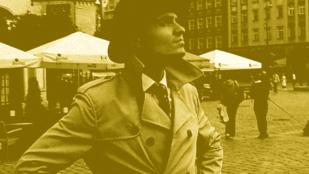 kadr z filmu kręć wrocław autorstwa szymona stępniewskiego, młody mężczyzna w jasnym prochowcu i kapeluszu stoi na wrocławskim rynku, patrzy w górę